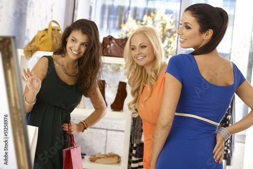 Pretty woman trying on blue dress at clothes store