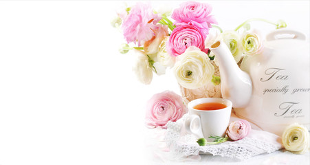 A cup of tea with teapot and ranunculus