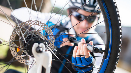 Male Cyclist Inflating Tire Of Bicycle