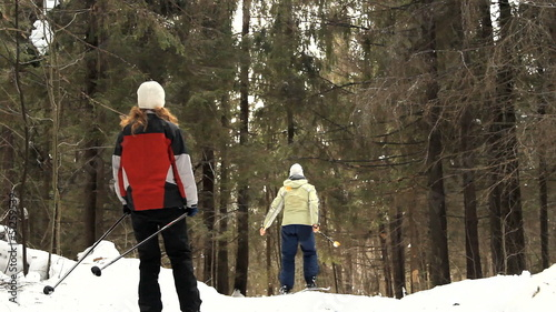 girls (persons) goes on skis on the snow road in the wood