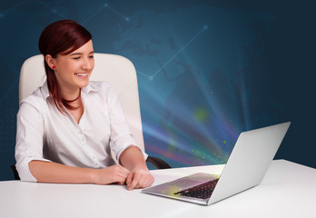 Beautiful woman sitting at desk and typing on laptop with abstra