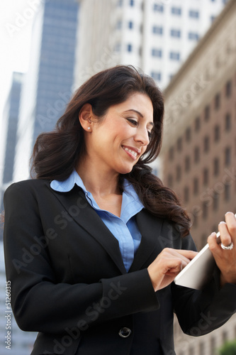 Businesswoman Working On Tablet Computer Outside Office