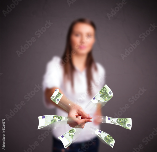 Pretty woman standing and throwing money