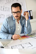 Architect working in office on blueprint