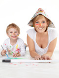 Cute boy and his mother painting with water colours