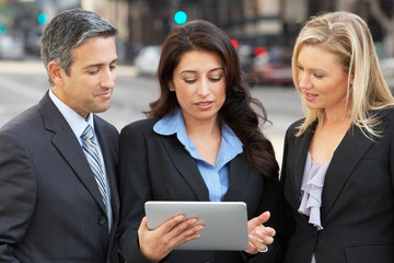 Businessman And Businesswomen Using Digital Tablet Outside