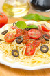 spaghetti with tomato sauce, cherry tomatoes and olives vertical