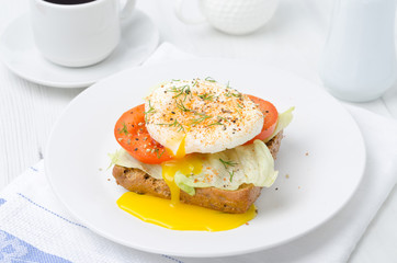 toast with tomato, lettuce and poached egg for breakfast