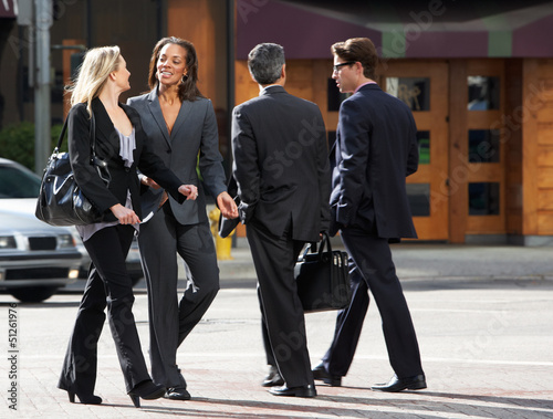 Two Businesswomen Chatting Whilst Crossing Street