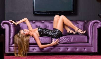 woman wearing a short dress relaxing on a sofa