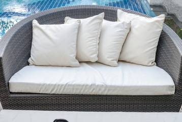 Relaxing seat sofa with pillows beside swimming pool.