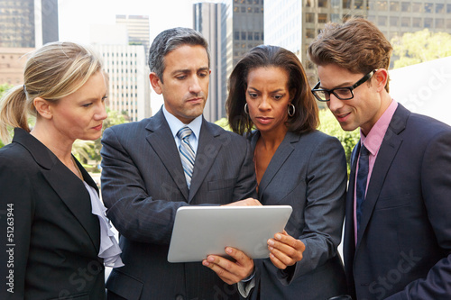 Businessmen And Businesswomen Using Digital Tablet Outside