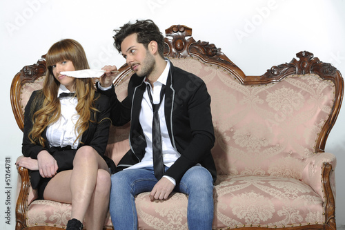 Engaged couple playing with feather