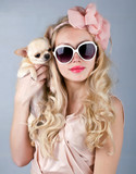 beautiful woman in sun glasses and small chihuahua in hands