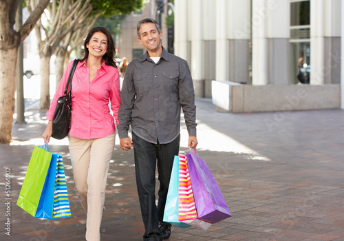 Couple Carrying Shopping Bags On City Street