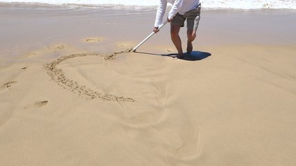 Sea  - painting a heart on the flat sand of the beach