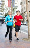 Male And Female Runners On Urban Street