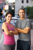 Portrait Of Male And Female Runners On Urban Street