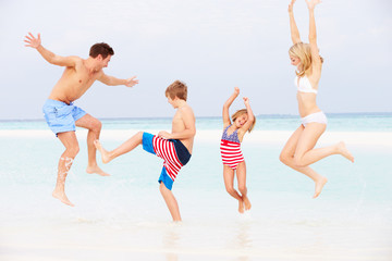 Family Having Fun In Sea On Beach Holiday