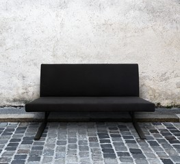 modern sofa on cobblestone street with wall behind