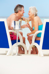 Senior Couple On Beach Relaxing In Chairs Drinking Champagne