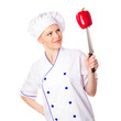 Smiling young chef in cap looking at red pepper, isolated