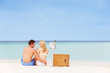 Couple On Beach With Luxury Champagne Picnic