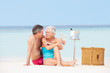 Senior Couple On Beach With Luxury Champagne Picnic