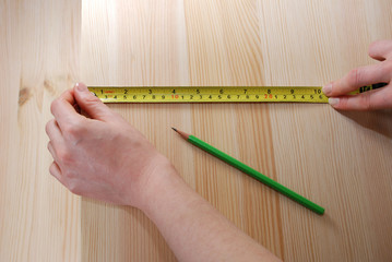 Two hands measure a wooden board with a steel tape measure