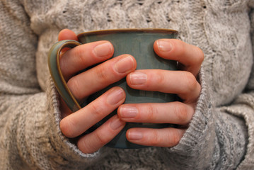 Two hands holding a mug of drink