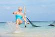 Senior Woman Splashing In Beautiful Tropical Sea