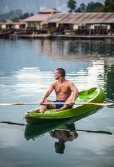 Strong young man in kayak on the picturesque lake in Thailand.