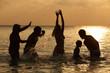 Silhouette Of Multi Generation Family Having Fun In Sea