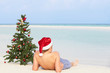 Boy Sitting On Beach With Christmas Tree And Hat