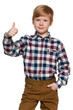 Red-haired young boy holds his thumb up