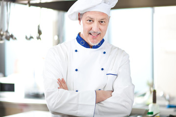 male chef smiling while standing in restaurant kitchen