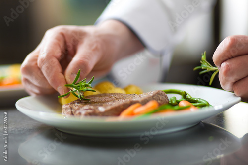 Leinwandbild Motiv Chef hands decorating a dish in restaurant kitchen
