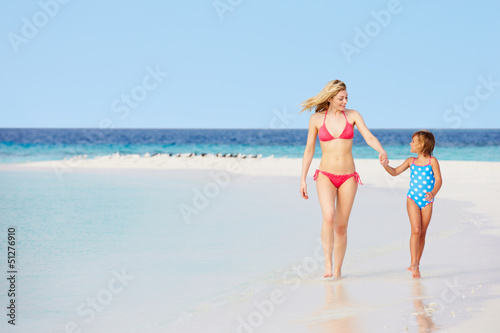 Mother And Daughter Walking On Beautiful Beach