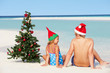 Boy And Girl Sitting On Beach With Christmas Tree And Hat