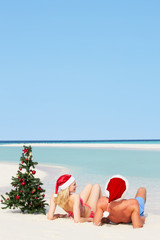 Couple Sitting On Beach With Christmas Tree And Hats
