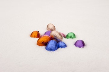 Colored chocolate Easter eggs in a snowy white background