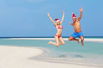 Couple Jumping On Beach Wearing Santa Hats
