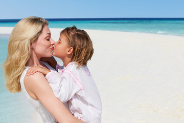 Mother And Daughter Hugging On Beautiful Beach