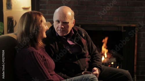Senior couple talking in front of fireplace