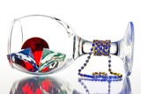 """Upside down with a glass of jewels on a white background"""