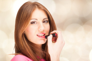 Beautiful woman applying lipstick