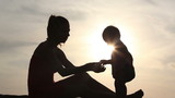 Silhouette  of woman haves game with kid over sunlight
