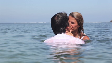 Cheerful couple in water  kissing each other