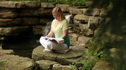 Woman reading near a waterfall
