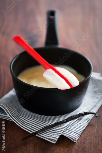 Making fresh vanilla custard in a metal pan, selective focus